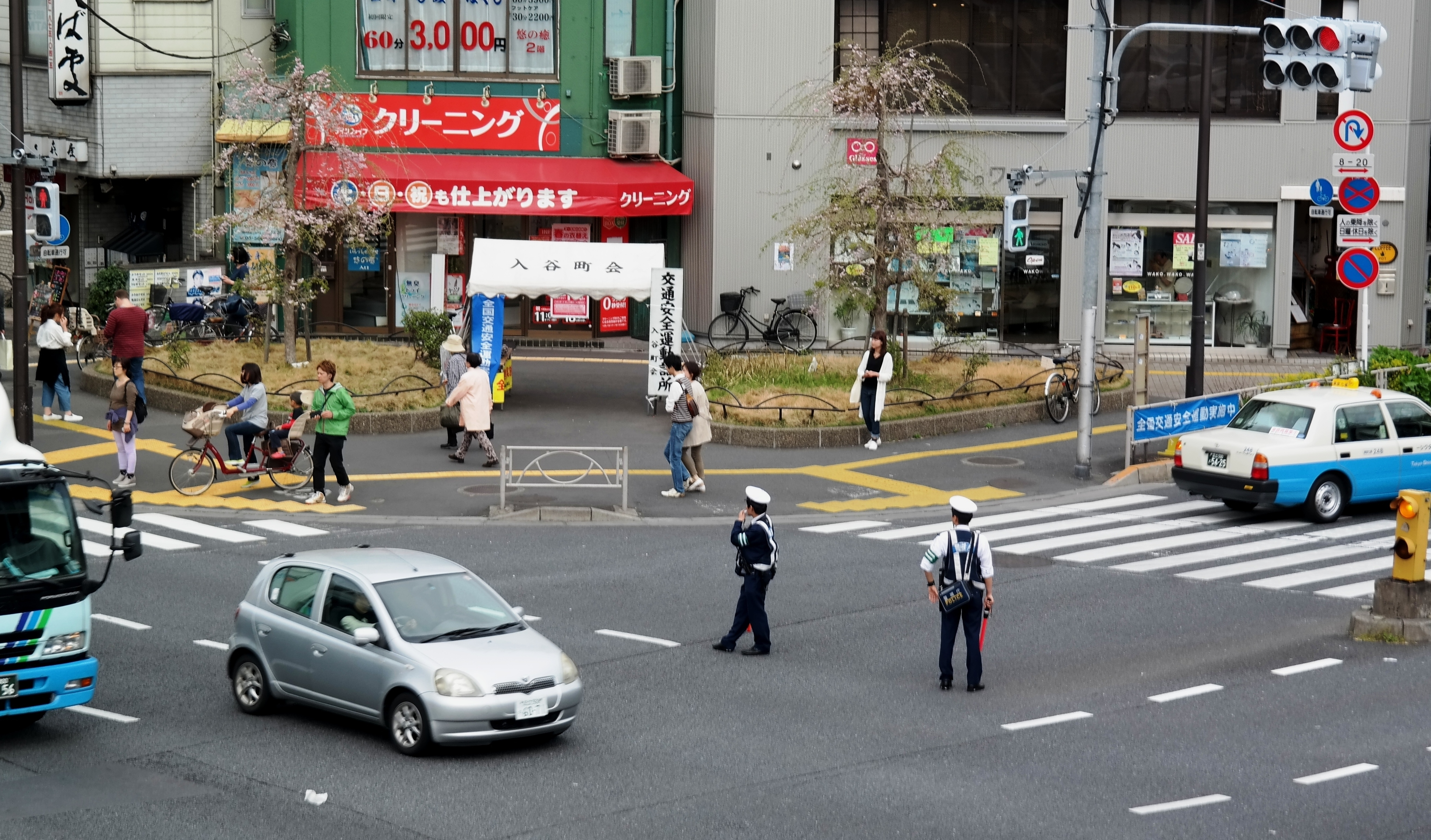 Cops - and traffic lights - directing traffic in Tokyo by kirsten bukager